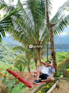Man in white t-shirt sitting on hammock