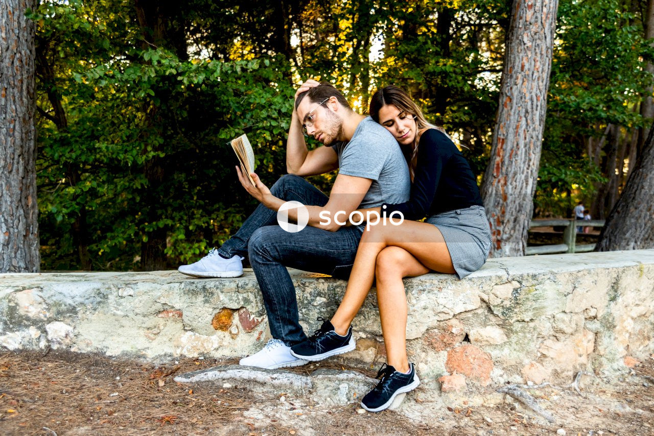 Woman sitting while hugging man reading book surrounded with tall and green trees
