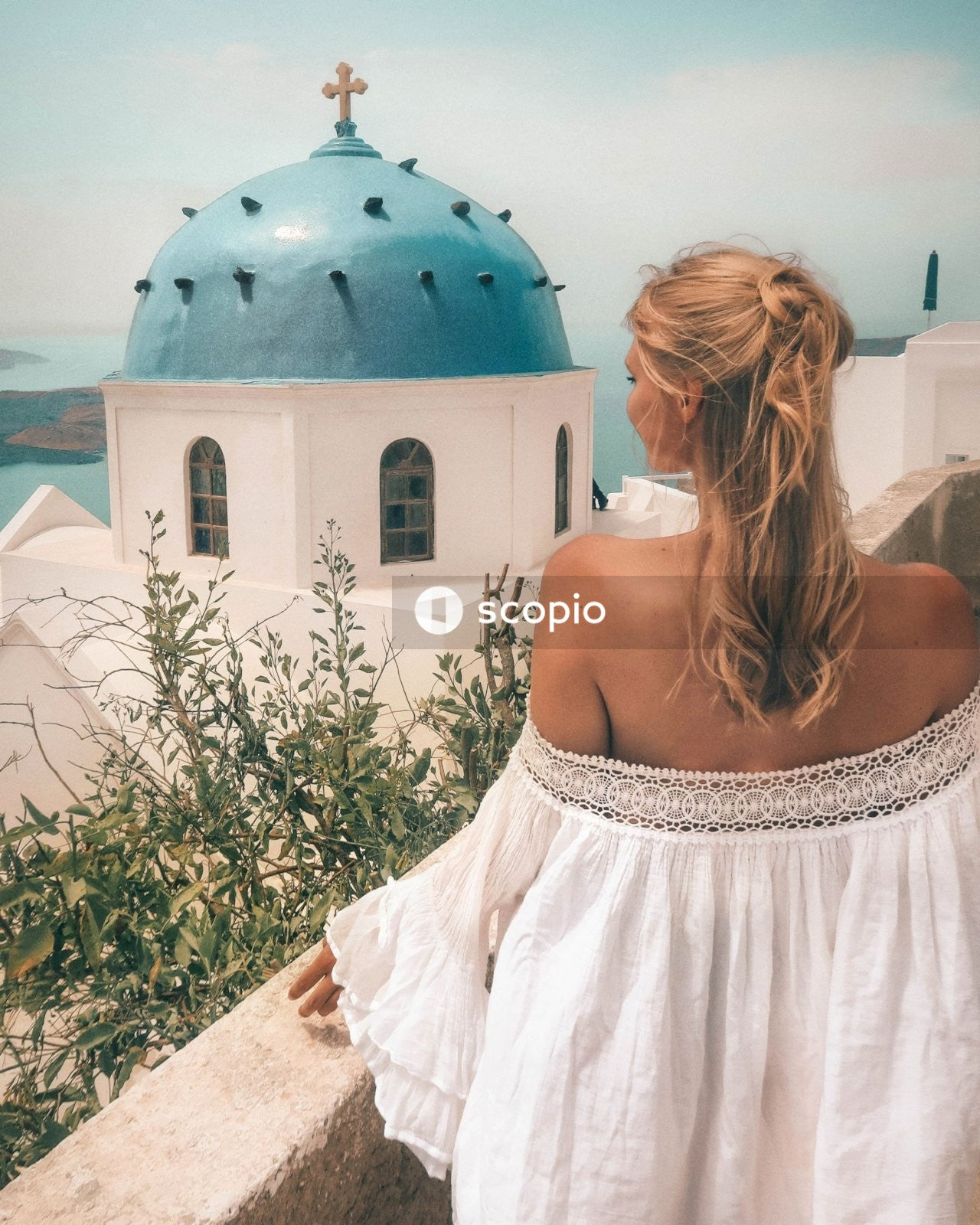 Woman wearing white off-shoulder blouse facing blue and white dome top building