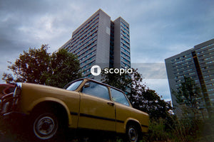 Yellow car parked near green tree and high rise building