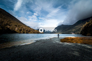 Person walking beside river near mountains