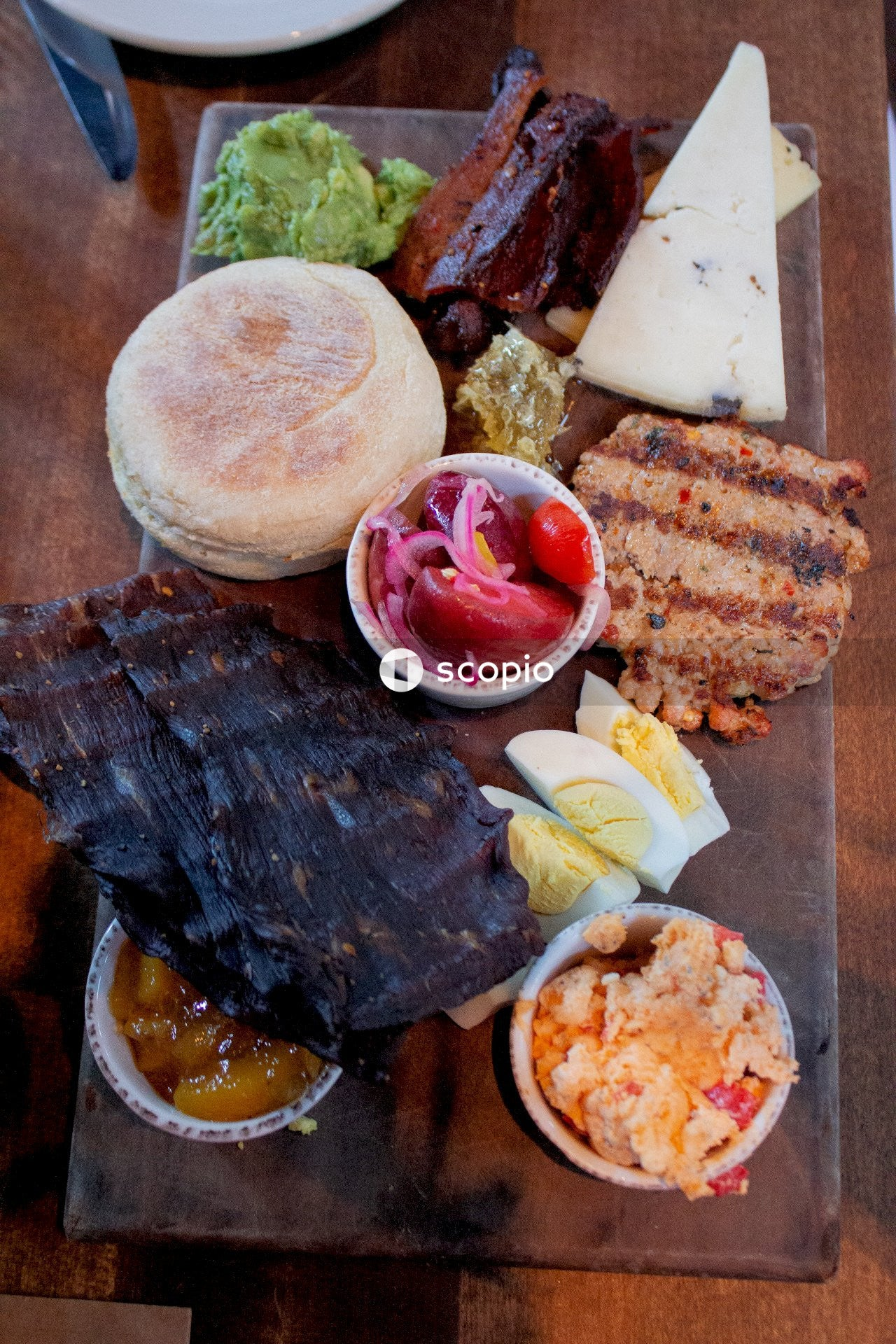 Steak near sliced boiled eggs, burger, cheese, and guacamole on wooden chopping board