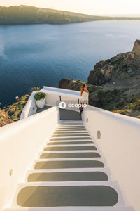 Woman in white shirt sitting on white concrete stairs