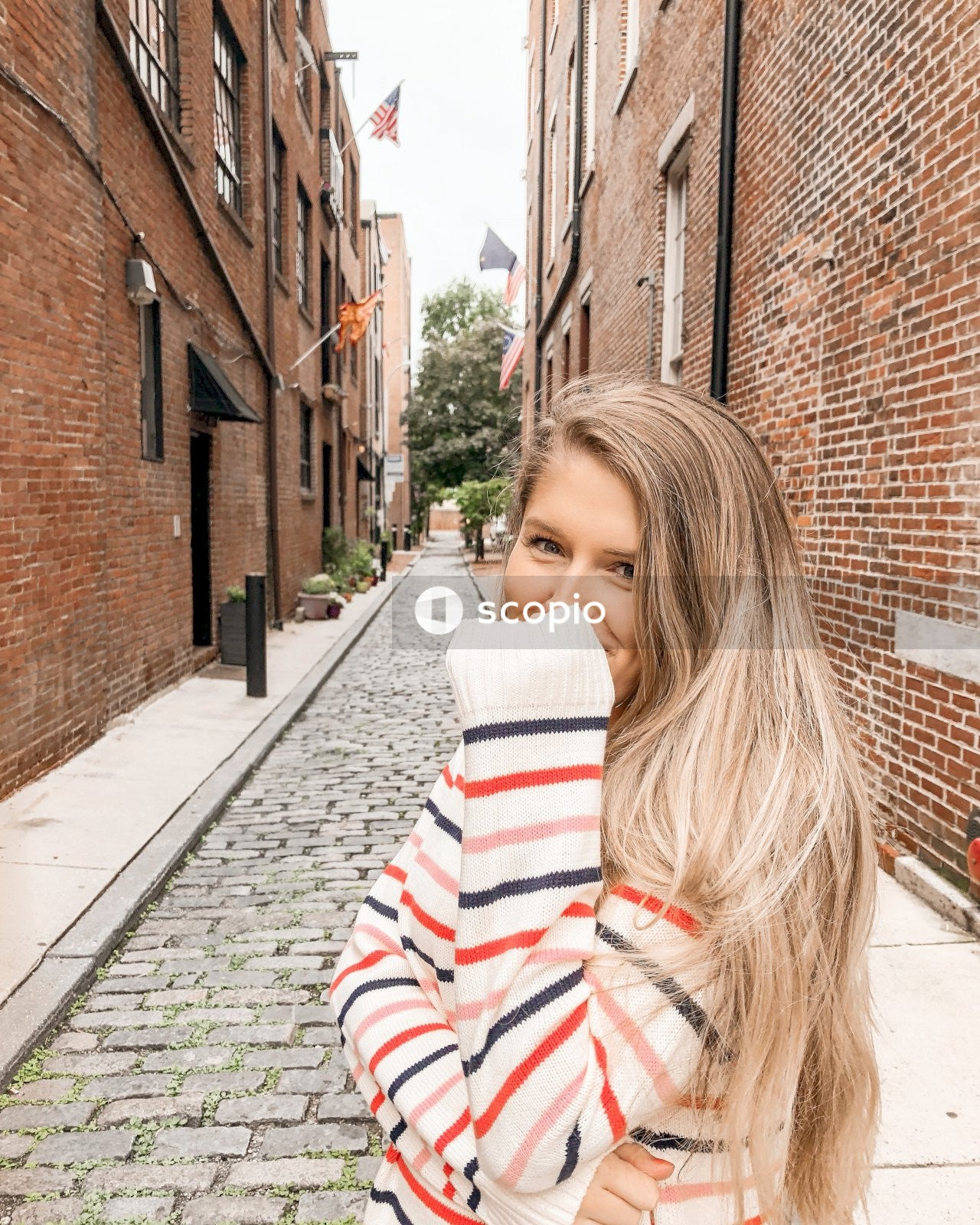 Woman in red and white striped long sleeve shirt standing on sidewalk