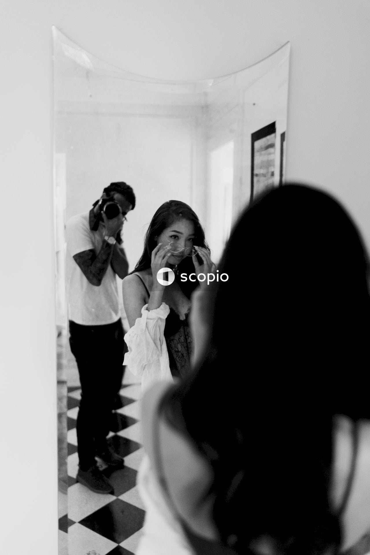 Woman standing in front of a mirror in front of man using camera
