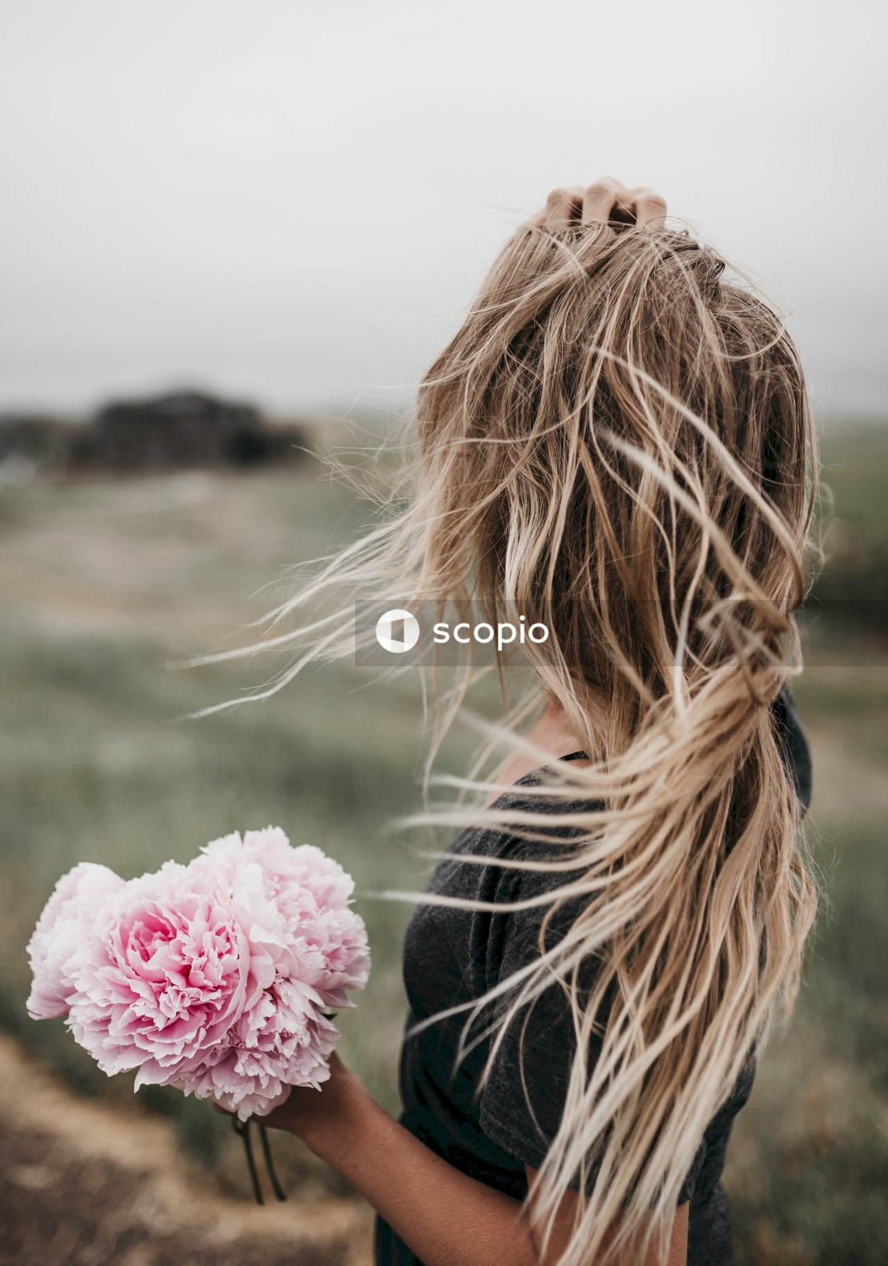 Woman in black long sleeve shirt with pink flower on her hair