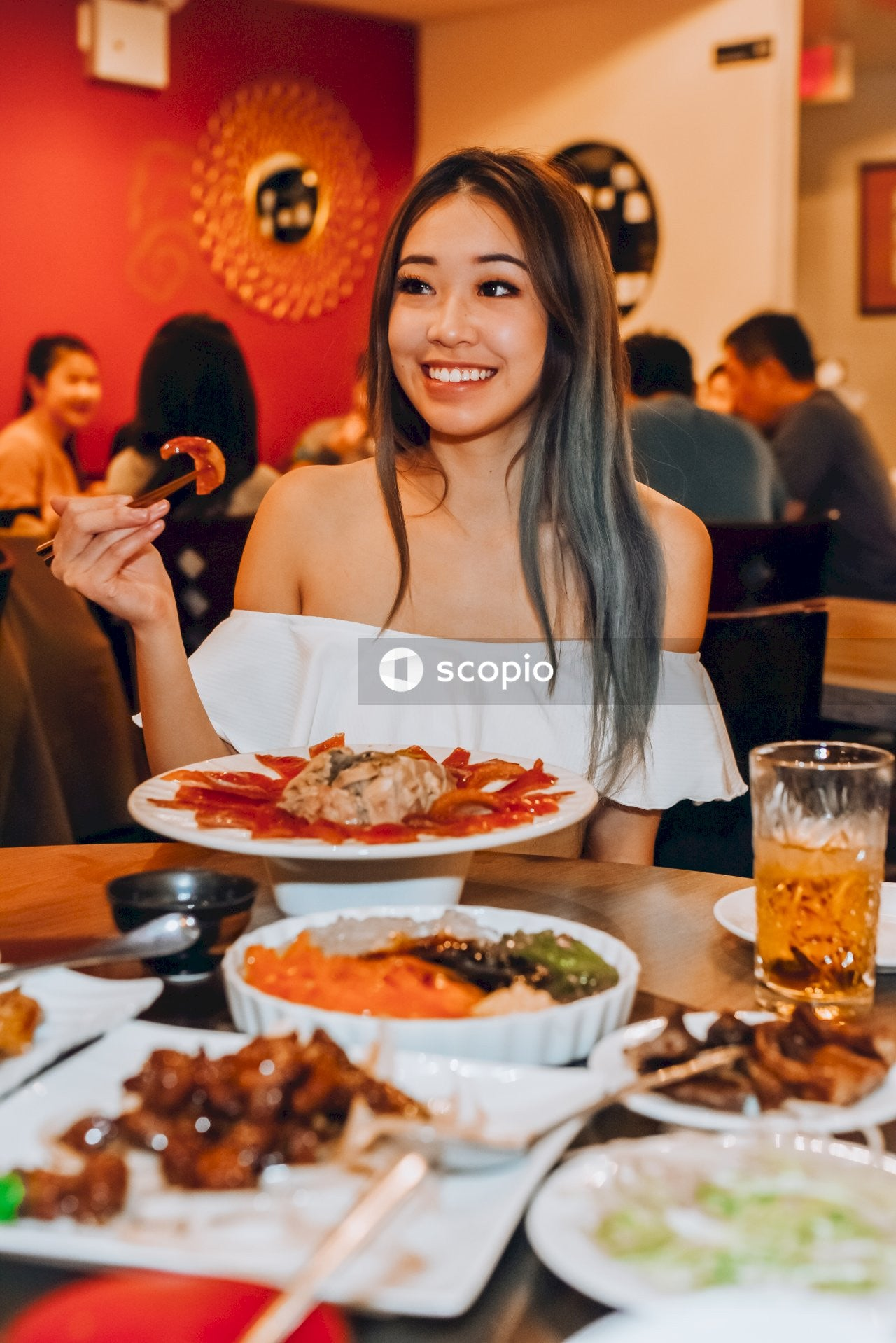 Smiling young woman eating asian food in restaurant