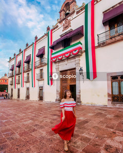 Woman in red dress standing in front of pink and white concrete building