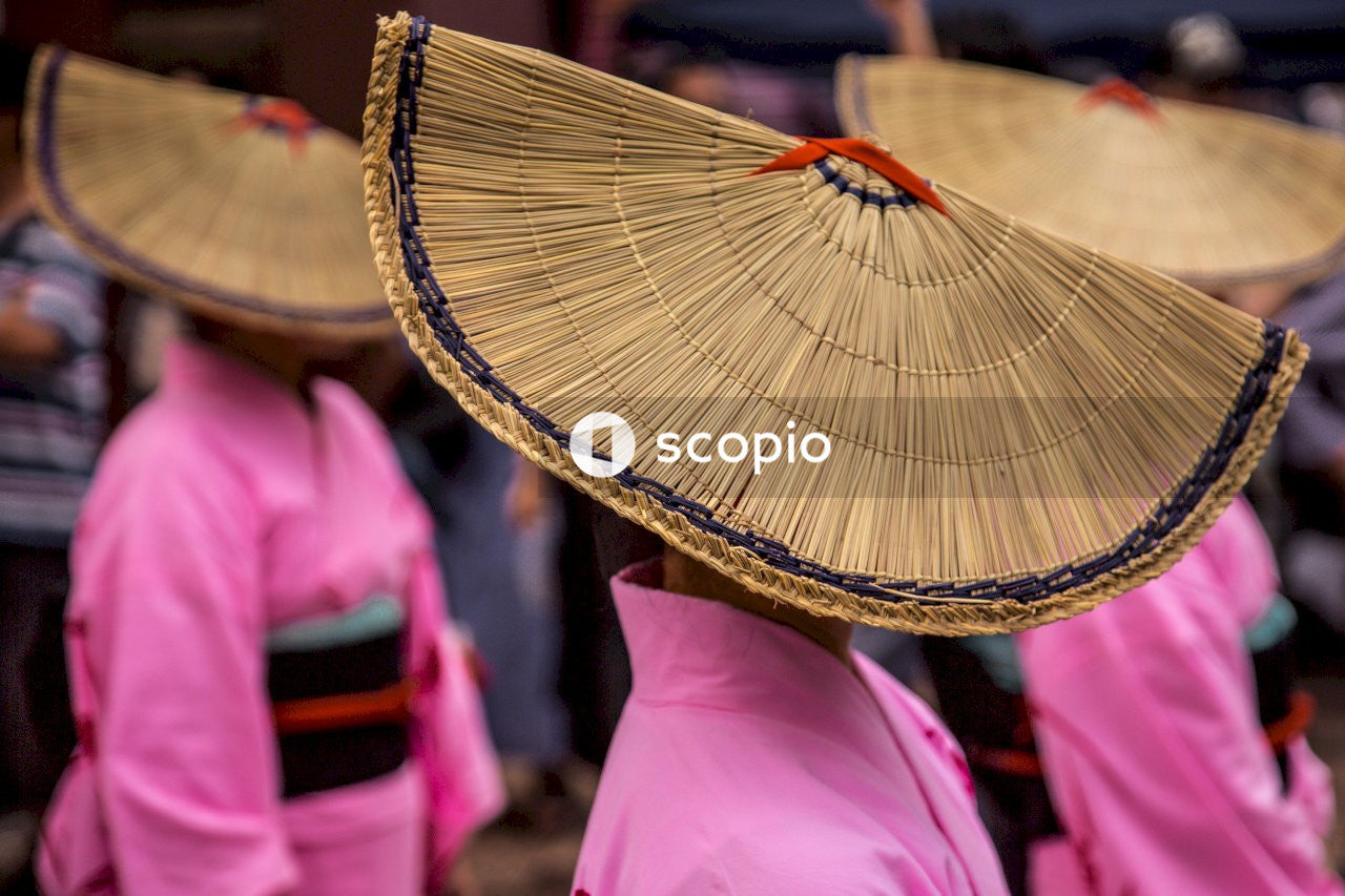 Person in pink dress holding brown hand fan