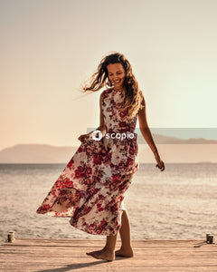 Woman in red and white floral dress standing on beach