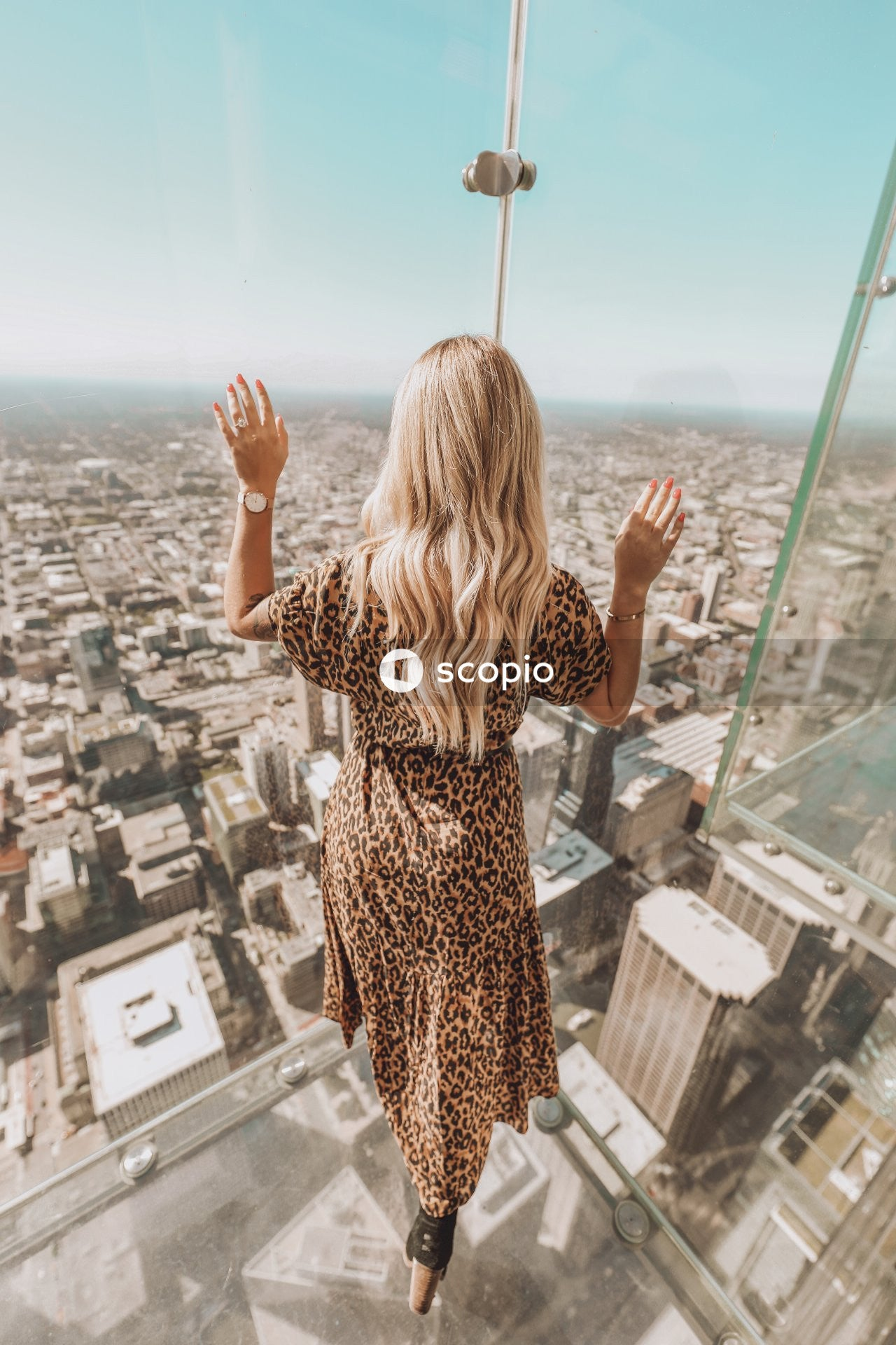 Woman in brown and black leopard print dress standing on top of building