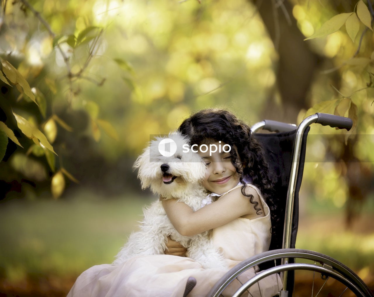 Girl smiling and hugging dog while sitting on wheelchair