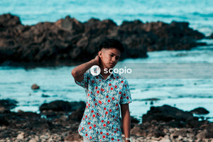 Man in red white and blue floral button up t-shirt standing on rocky shore