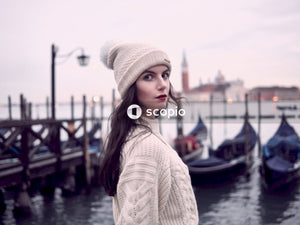 Woman wearing white cable-knit sweater and bobble hat looking fierce