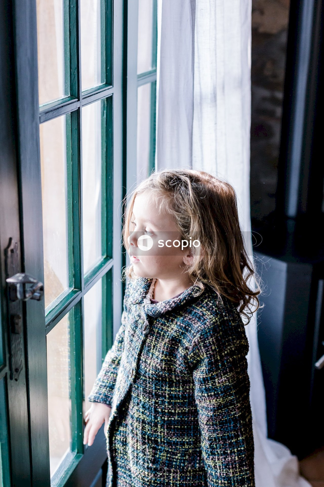 Girl in blue and white sweater standing beside green wooden door
