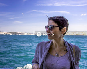 Woman wearing sunglasses standing on boat