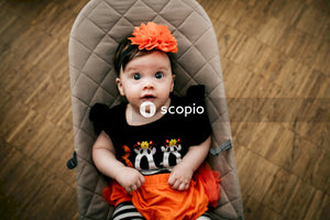 Baby in black and orange crew neck t-shirt lying on brown sofa
