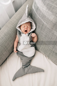 Baby in white onesie lying on gray couch