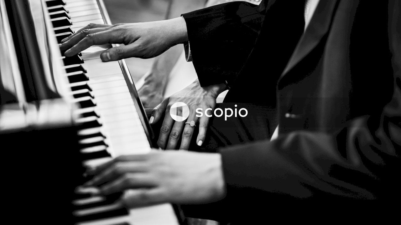Grayscale photo of man playing piano
