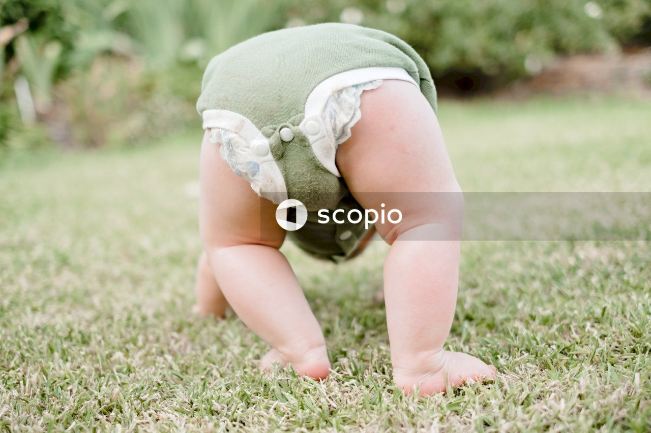 Baby in white dress on green grass