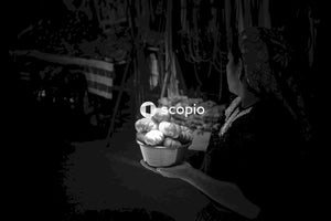 Grayscale photography of woman holding bucket with food inside