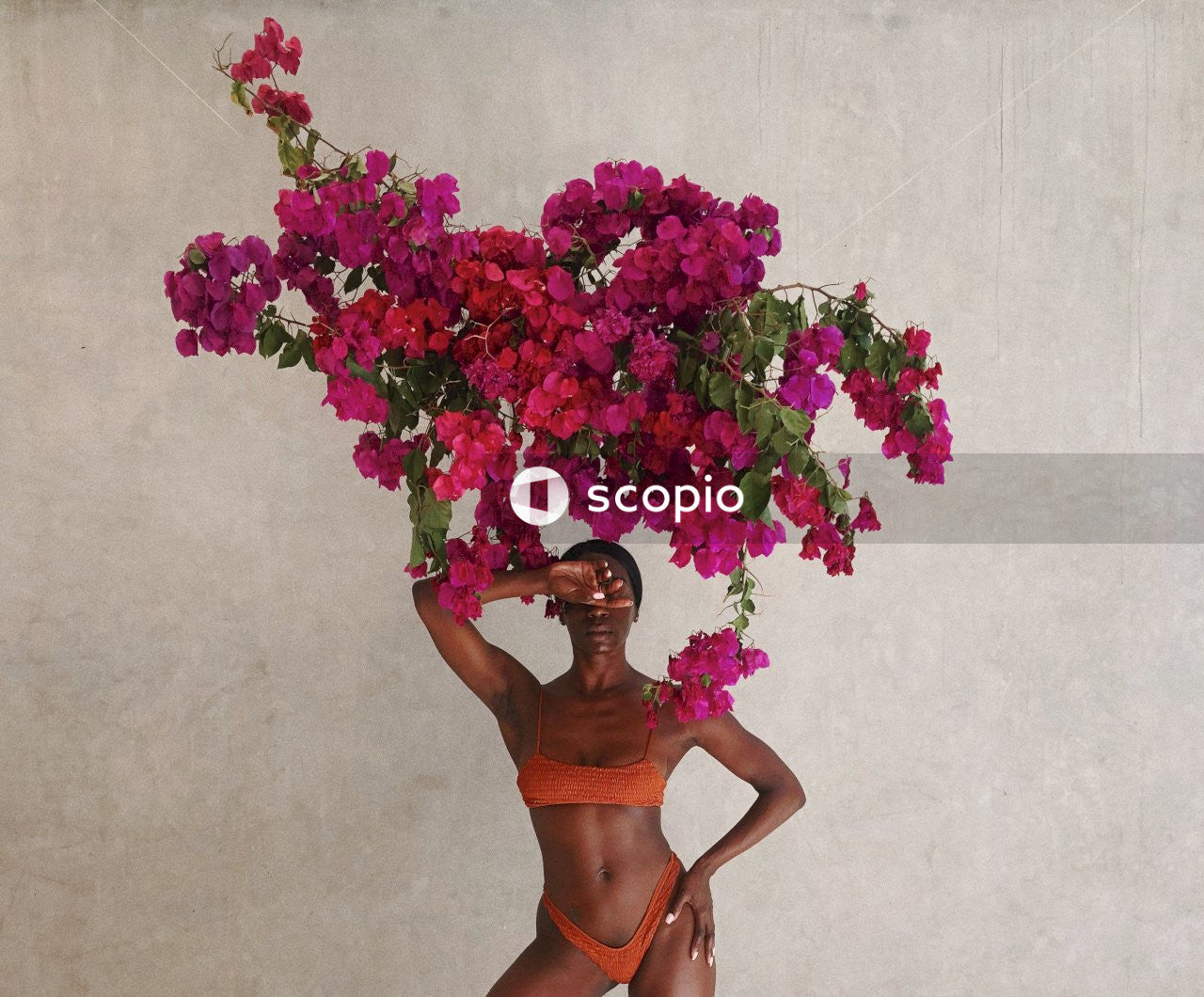 Woman in orange bikini standing beside pink flowers