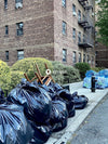 Black garbage bag near brown brick building