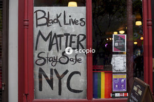 """black lives matter"" and ""lgbtq"" pride banners at a store window"