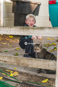 Boy in black jacket and blue denim jeans sitting on concrete bench with brown tabby cat