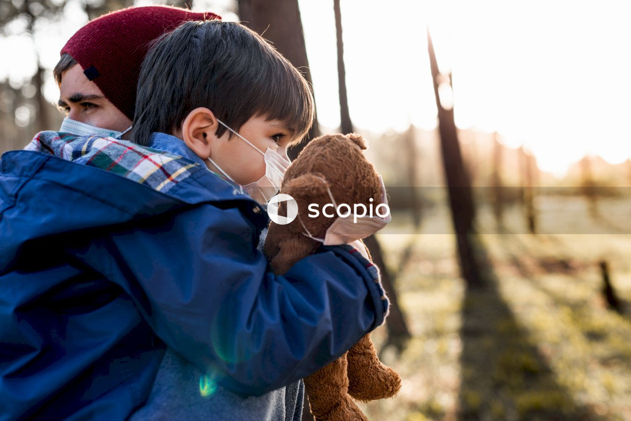 Boy in blue jacket holding brown bear plush toy