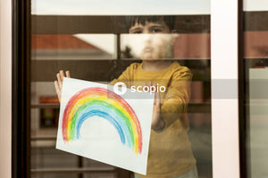 Boy showing his rainbow drawing through the window