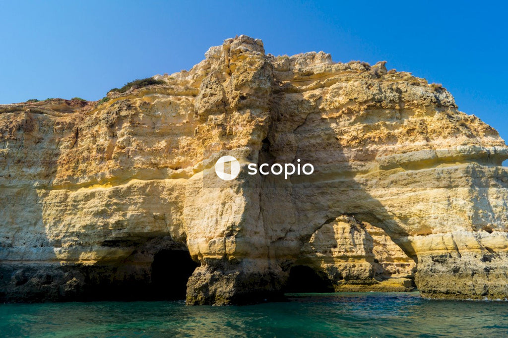 Brown rock formation on blue sea under blue sky