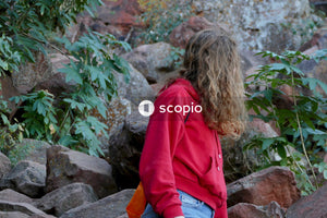 Woman in red jacket and blue denim jeans sitting on rock