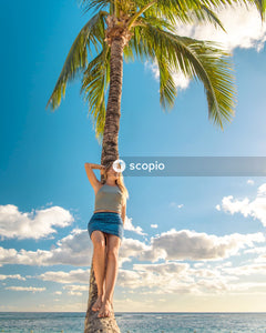 Woman in blue denim shorts standing on palm tree