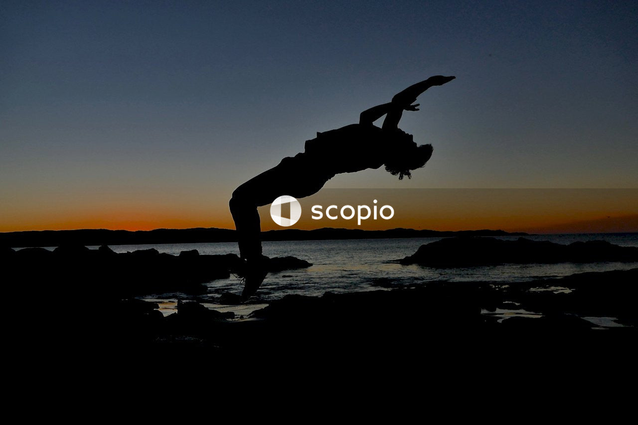 Silhouette of man jumping on beach during sunset