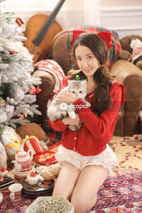 Girl in red sweater holding white bear plush toy