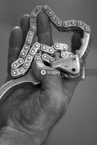 Grayscale photo of person holding metal tool