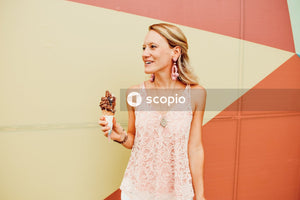 Woman in white and red floral spaghetti strap top holding chocolate ice cream