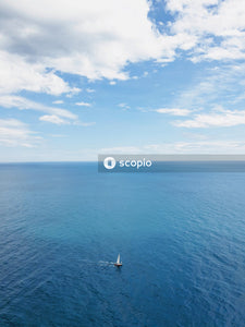 White sailboat on sea under blue sky