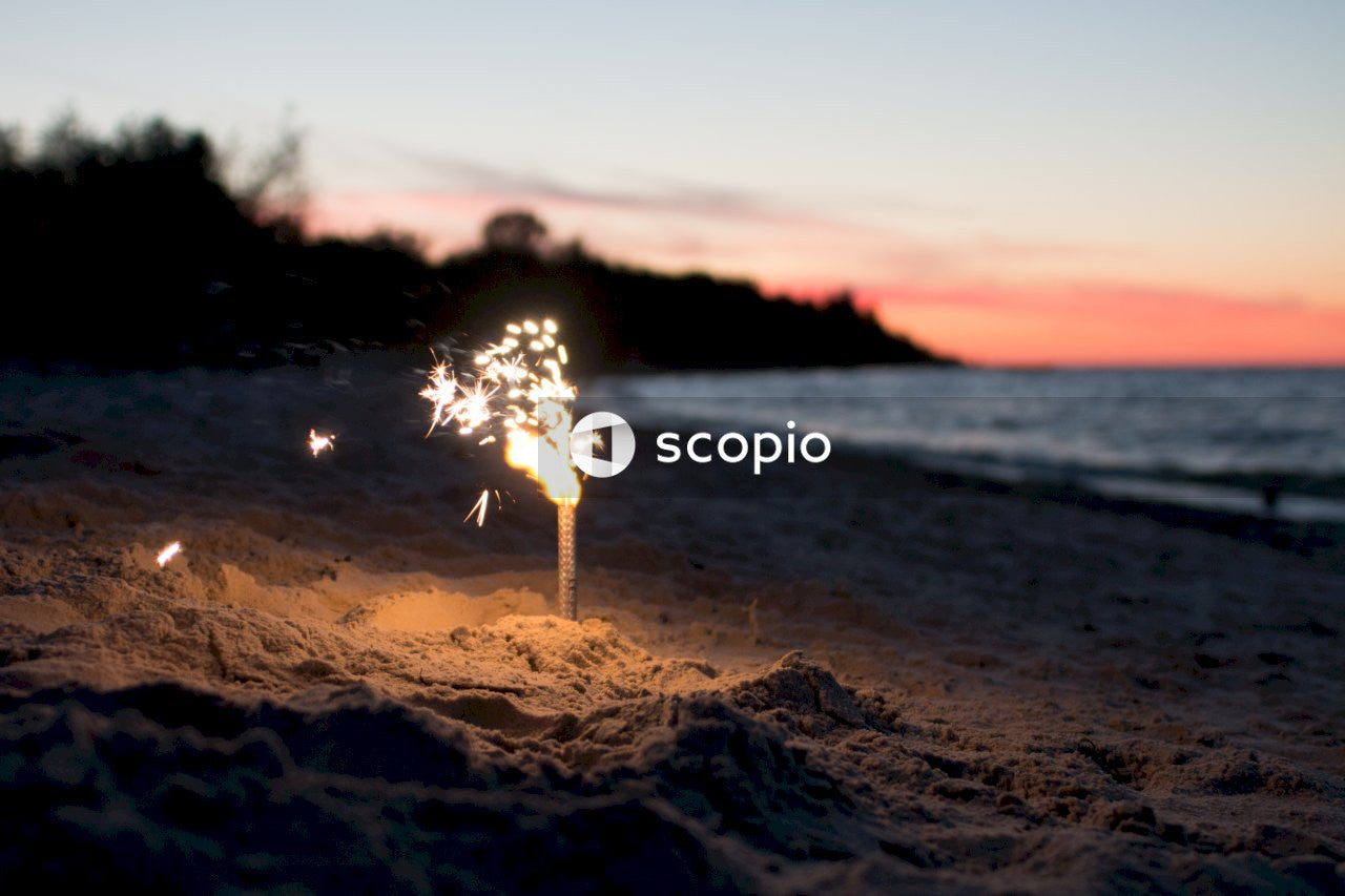 Silhouette of person holding sparkler near body of water during sunset