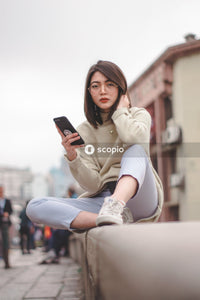 Woman in sweater and pants sitting on rail while holding smartphone