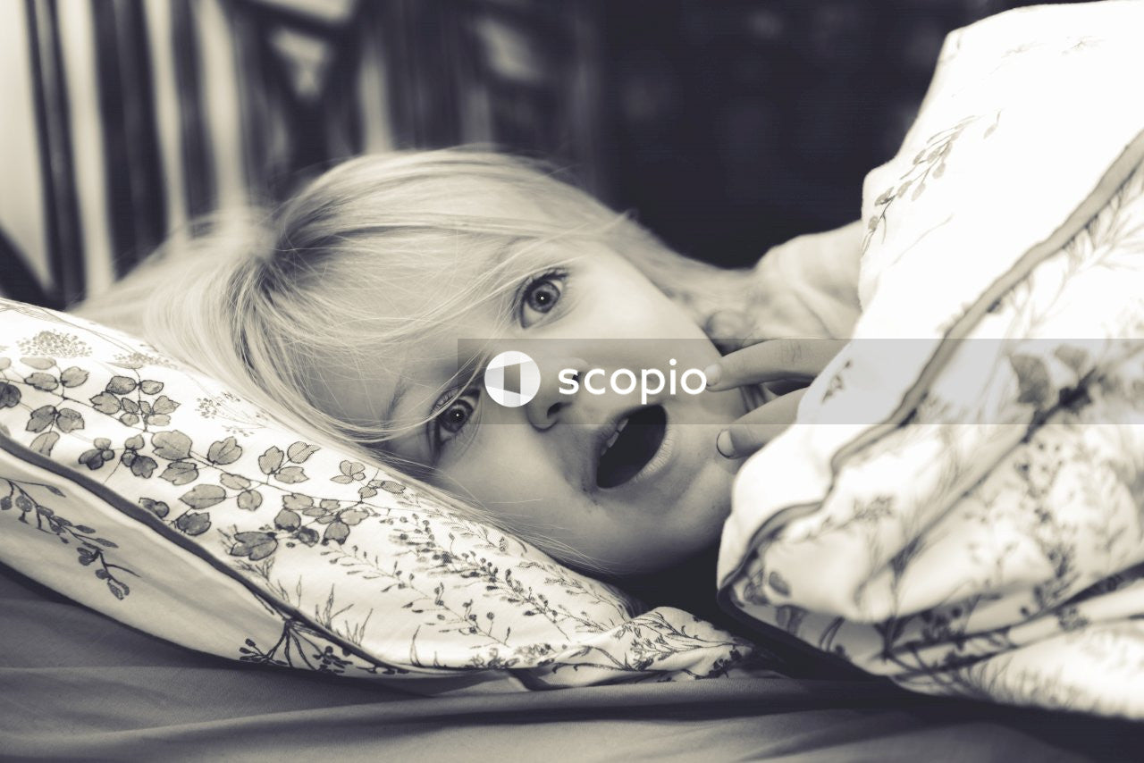 Grayscale photo of girl lying on bed