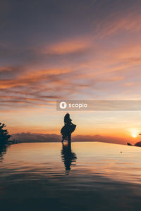 Silhouette of woman standing at edge of infinity pool at sunset