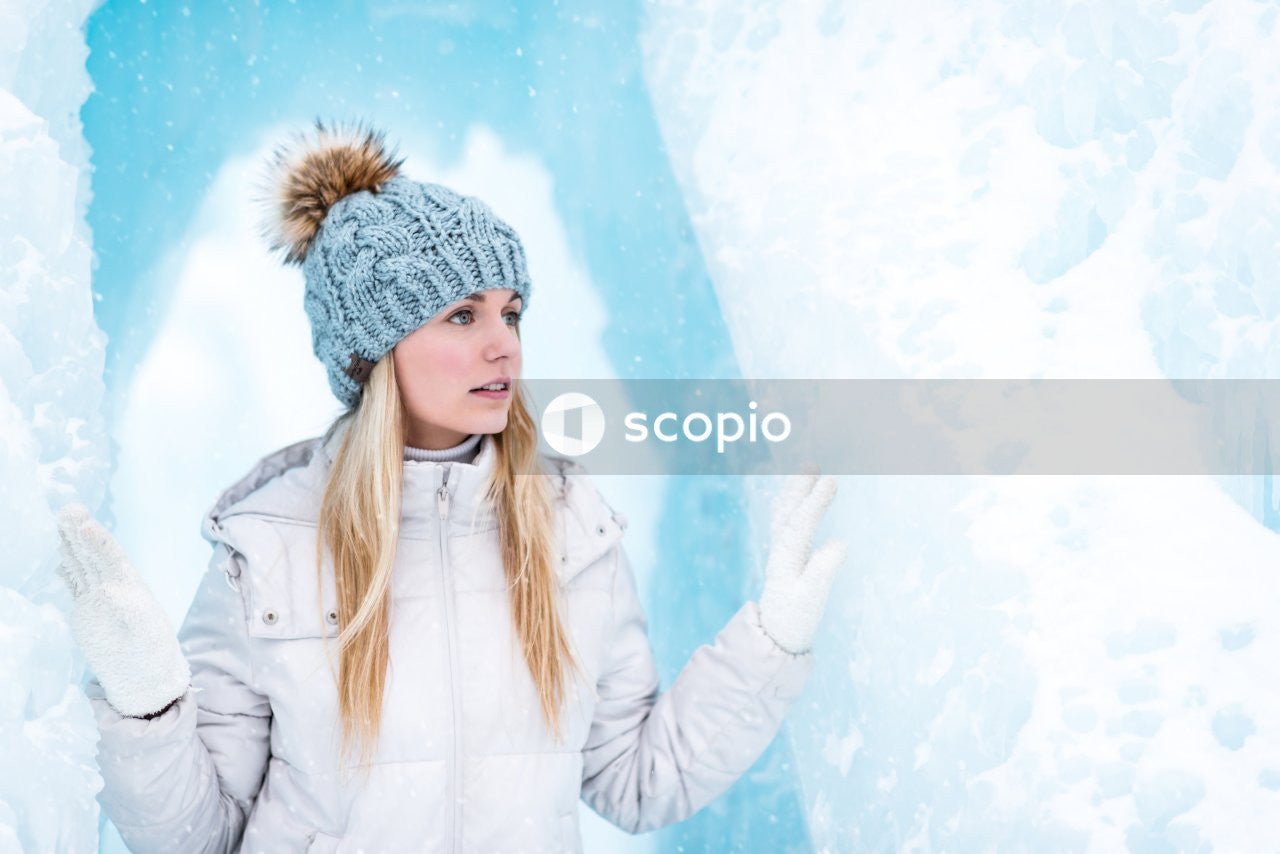 Woman in white winter coat and gray knit cap standing on snow covered ground