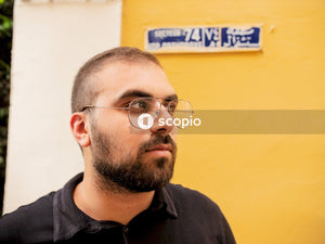 Man looking with yellow wall and street name behind him in beirut