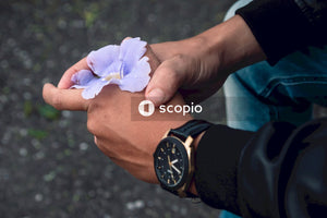 Man holding purple hibiscus flower