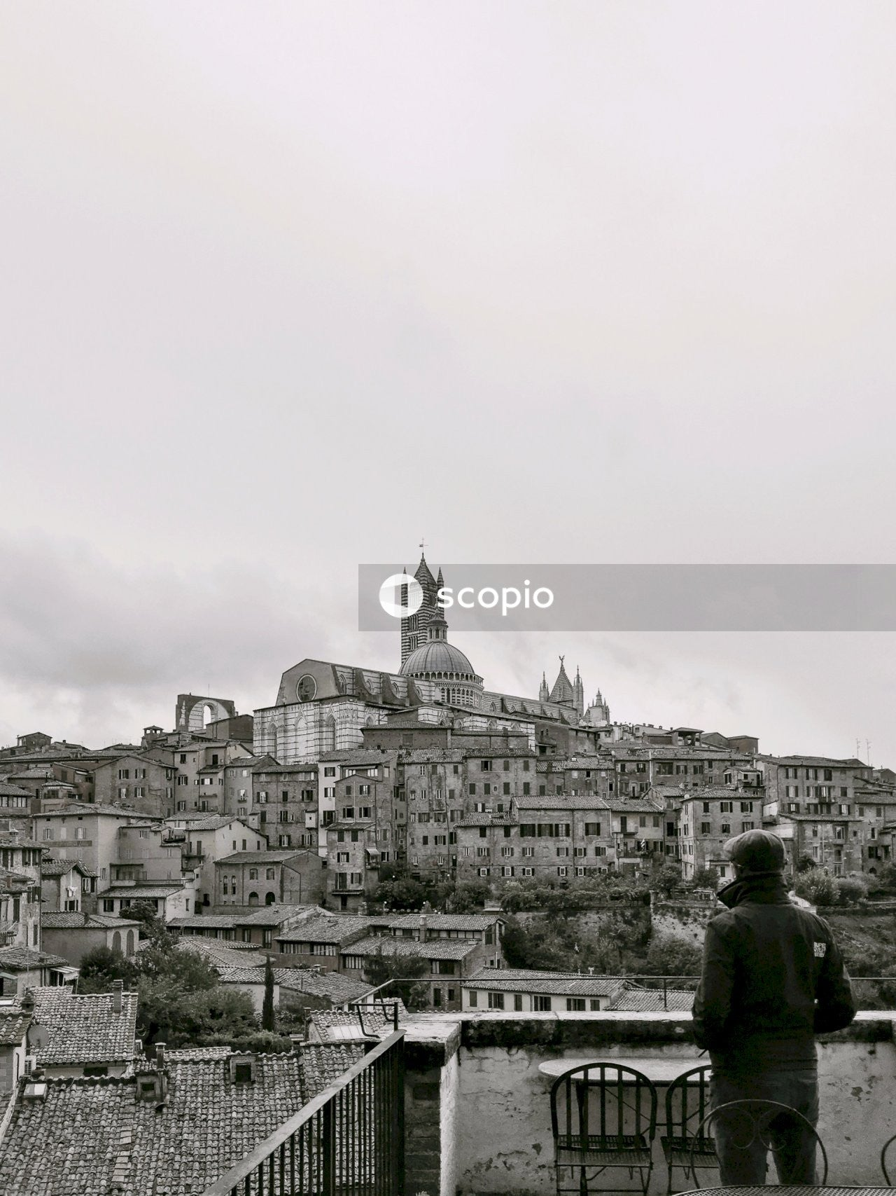Grayscale photo of a city at a hill