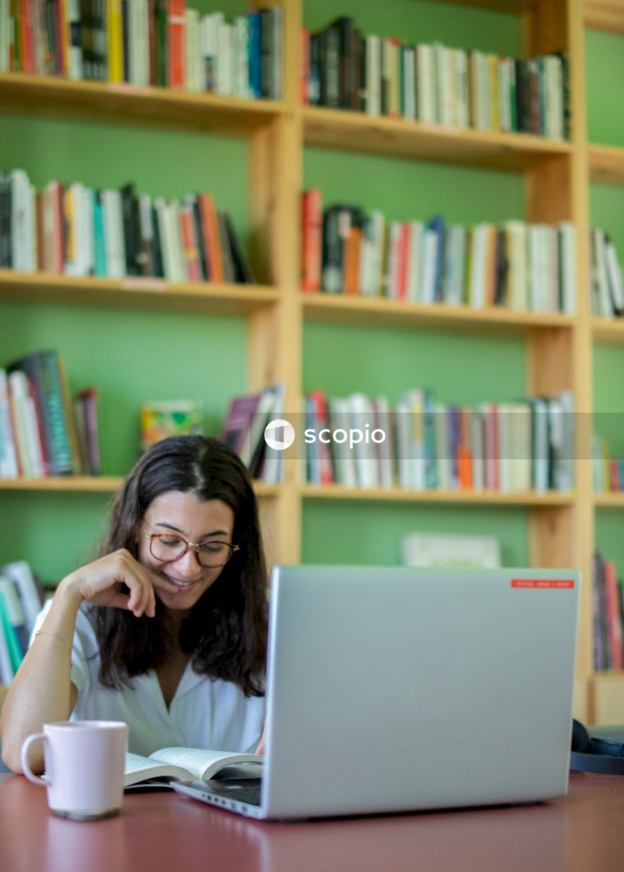 Woman smiling while working on her laptop