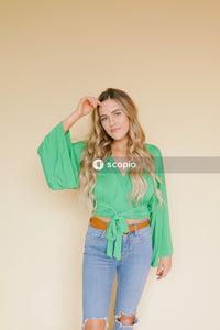 Woman in green button up shirt and blue denim jeans
