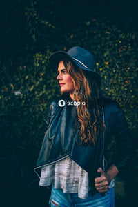 Woman in black leather jacket and black fedora hat standing near green plants